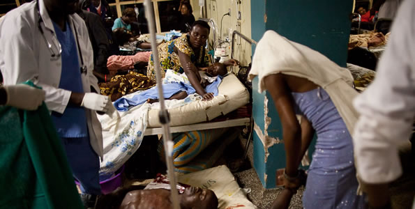 Doctors treat victims at Mulago hospital in Kampala in Kampala late on July 11, 2010 after twin bomb blasts tore through crowds of football fans watching the World Cup final, killing 64 people, including an American, and wounding scores others.