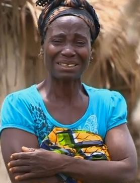 A face of grief. This woman in Liberia wails uncontrollably as a neighbour is removed for burial in a most undignified, but necessary manner. The impact of Ebola on communities.