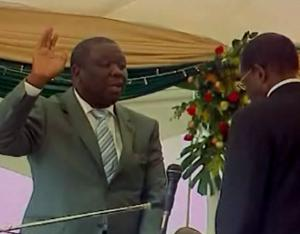 PM Morgan Tsvangirai takes the oath before arch rival Mugabe