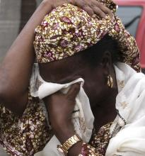 A woman weeps in the aftermath of the bomb blast at the UN Office in Abuja